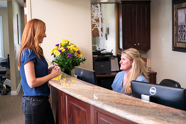 A new patient talking to our receptionist at Cassity & Legacy Implants and Periodontics in South Ogden and Kaysville, UT
